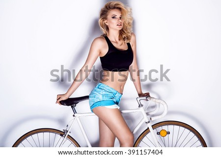 Attractive sexy blonde woman on a bike. Fitness photo - stock photo