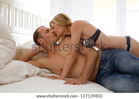 Attractive sexy couple being intimate and kissing while laying down on a white bed in a home bedroom.