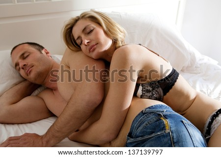 Attractive sexy couple hugging while laying down and relaxing on a white bed in a hotel bedroom.