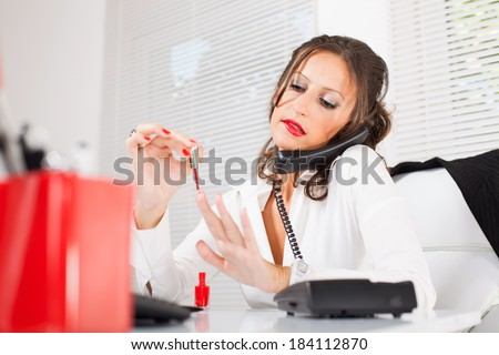 Attractive sexy secretary lacquered nails  in the office and talking on the phone and biting lips.