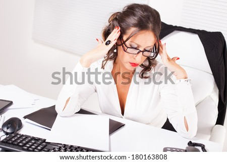 Attractive sexy secretary with glasses sitting at the table, hold on to your head  and thinking