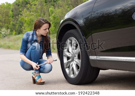 Attractive sexy slender young woman checking out a flat tyre on her car as she kneels in the road holding the wheel spanner - stock photo