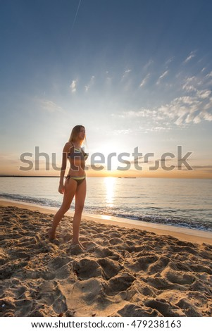 attractive sexy slim long legs woman in bikini walking on sand on lonely beach on sunrise sunset