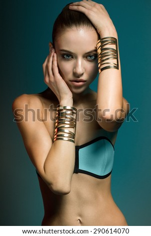 attractive sexy sports model with long brunette natural hair, beautiful eyes, full lips, perfect skin posing  in studio in blue swimwear and golden bracelets, beauty photo shoot, retouched image - stock photo