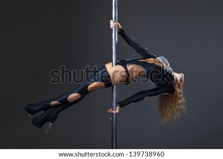 Attractive sexy woman pole dancer performing against grey background