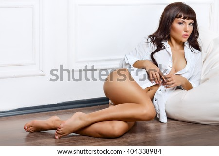 Attractive sexy woman posing in studio. Girl with long hair and perfect fit body. Girl looking at camera, sitting  - stock photo