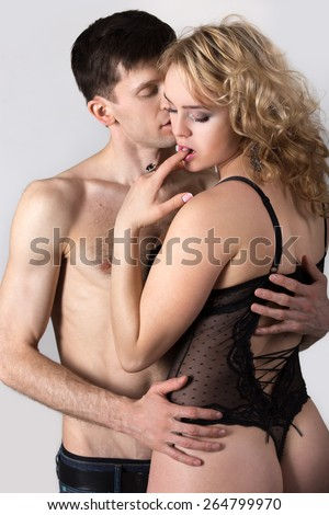 Attractive sexy young couple hugging, feeling pleasure, handsome guy in jeans caressing with passion blond girl in black lace underwear