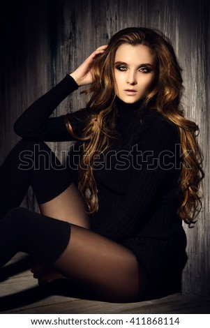 Attractive sexy young woman alluring by the dark grunge background.  Beauty, fashion. Cosmetics, dark make-up. Long hair.