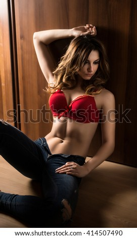 Attractive sexy young woman in jeans and red bra sitting on the floor in semidarkness. Sensual redhead posing provocatively against wooden wall. Beautiful perfect body girl with long hair, solitude - stock photo