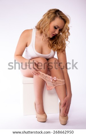 attractive sexy young woman sitting on a stool with a panty on the legs and heels - stock photo