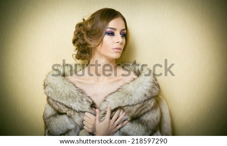 Attractive sexy young woman wearing a fur coat posing provocatively indoor. Portrait of sensual female with creative haircut, studio shot. Beautiful girl covered only with a fur exposing her shoulders