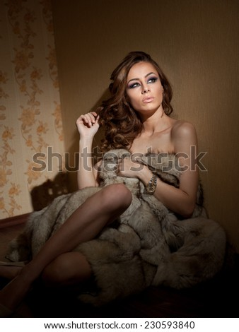 Attractive sexy young woman wrapped in a fur coat sitting in hotel room. Portrait of sensual female daydreaming near a wall. Beautiful girl covered only with fur exposing her shoulders - stock photo