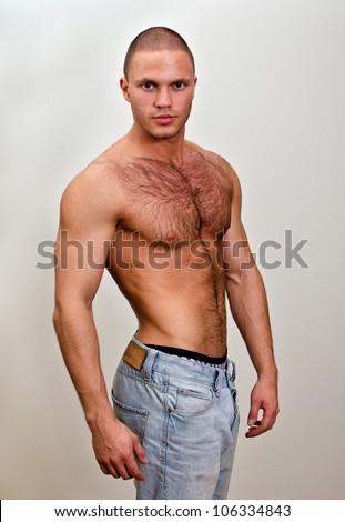 Attractive shirtless male in jeans, on grey background