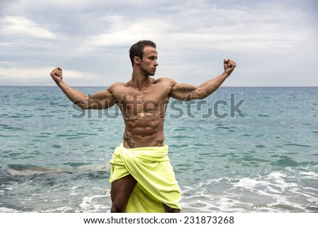Attractive shirtless muscleman on the beach covering with towel in muscular pose - stock photo