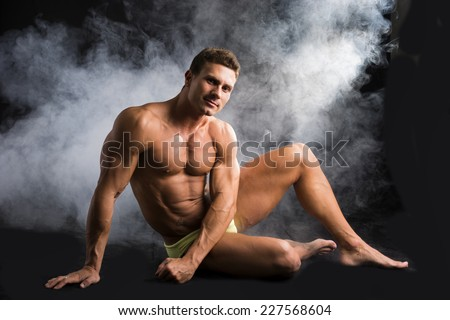 Attractive shirtless muscular man sitting on the floor in bathing suit on dark background - stock photo