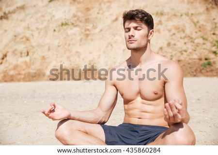 Attractive shirtless young man meditating on the beach - stock photo