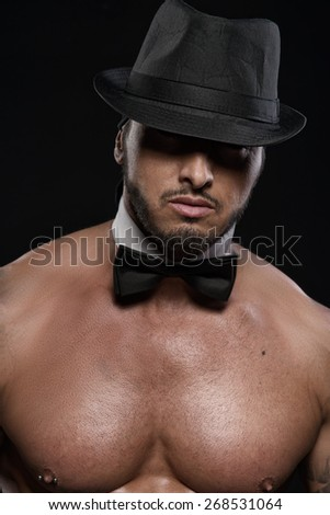 Attractive shirtless young man with black bowtie and top hat on dark background - stock photo