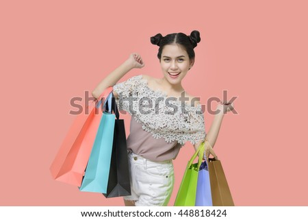 Attractive shopper woman holding shopping bags on salmon background - stock photo