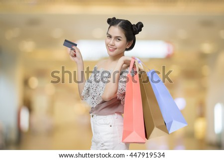 Attractive shopper woman holding shopping bags with Credit Card - stock photo