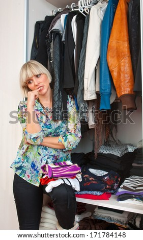 attractive short hair blond woman in front of closet full of clothes - stock photo