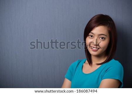 Attractive sincere young Asian woman standing looking directly into the lens with a quiet smile on a dark grey background with corner vignetting and copyspace - stock photo