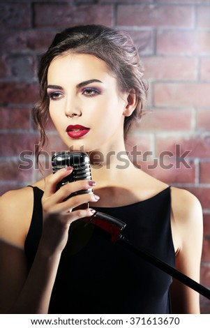 Attractive singing woman  on brick wall background, close up