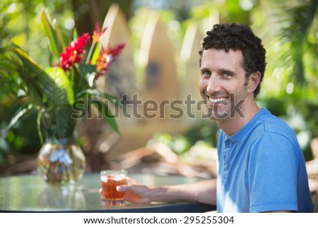 Attractive single adult male with drink in Maui Hawaii - stock photo