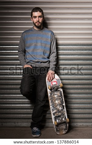 Attractive skater leaning against metal shutters and holding his board in the skate park - stock photo