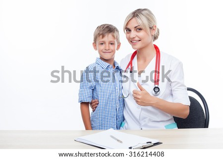 Attractive skilled doctor is examining health of child. She is sitting at the table and giving her thumb up. The boy and woman are smiling and embracing. Isolated and copy space in left side - stock photo