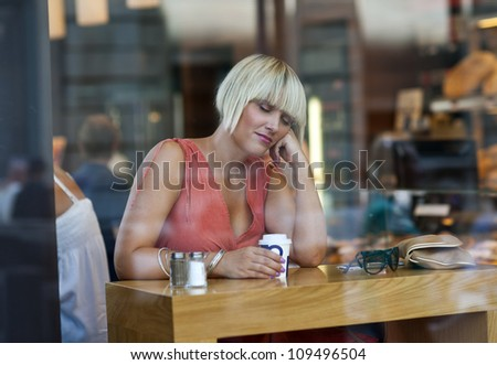 attractive sleepy woman drinking morning coffee in cafe - stock photo