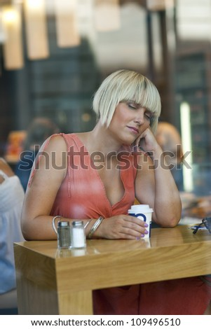 attractive sleepy woman drinking morning coffee in cafe window - stock photo