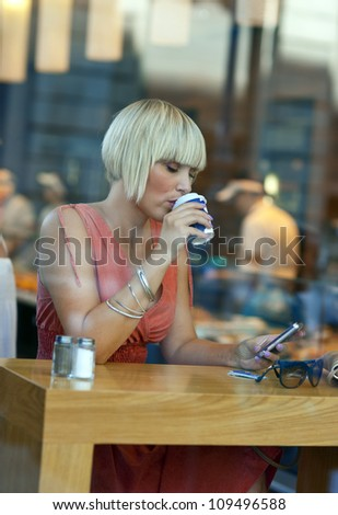 attractive sleepy woman drinking morning coffee in cafe window with mobile phone - stock photo