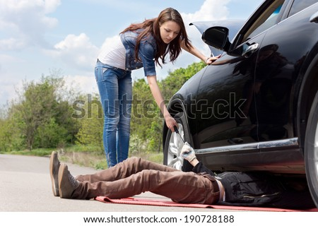 Attractive slender young female driver assisting a mechanic working on her car after it had a breakdown handing him a socket spanner - stock photo