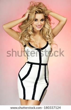 Attractive slim beautiful blonde woman posing in studio wearing elegant dress, looking at camera. - stock photo