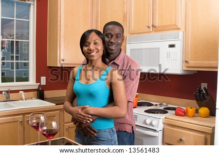 Attractive smiling African American couple standing in a kitchen. Horizontally framed shot with the man and woman looking at the camera.