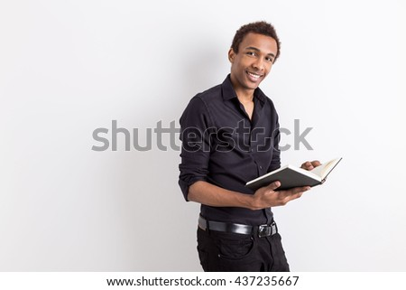Attractive smiling african american guy holding book on white background with copy space. Education concept