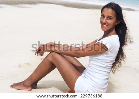 Attractive Smiling Asian Indian Woman Wearing White Shirt and Shorts Resting on White Beach Sand While Looking at the Camera. - stock photo