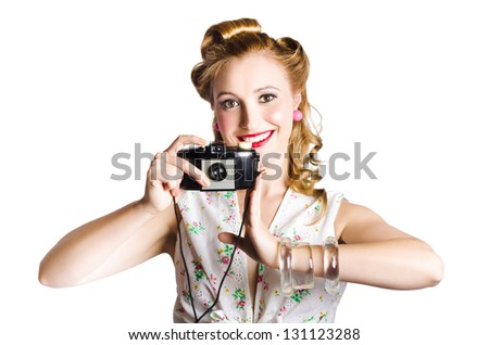 Attractive smiling blond woman taking a picture with a black retro film camera on white background - stock photo