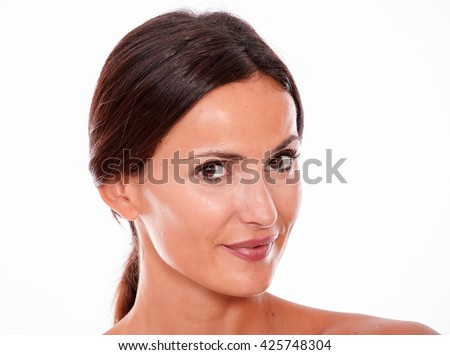 Attractive smiling brunette young woman only looking at the camera with her long straight hair tied back on a white background - stock photo