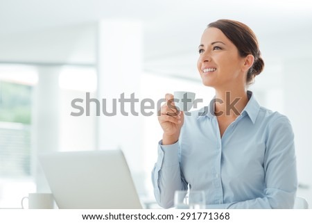 Attractive smiling business woman sitting at office desk, holding a cup of coffee, she is relaxing and looking away - stock photo