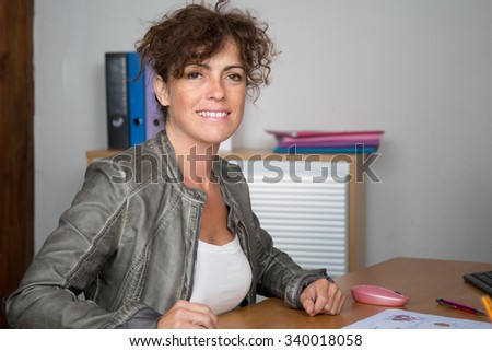 Attractive smiling  business woman using computer at work desk - stock photo