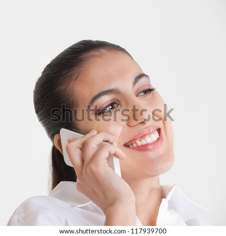 Attractive smiling business woman using her smartphone to make a call - stock photo
