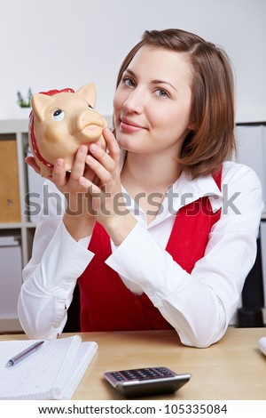 Attractive smiling business woman with piggy bank at her desk - stock photo