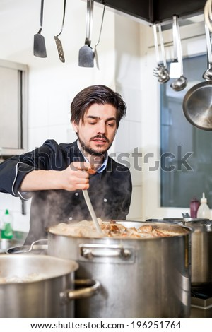 Attractive smiling cook or chef stirring a huge stainless steel pot of stew or casserole on a hob in a commercial kitchen at a restaurant or hotel - stock photo