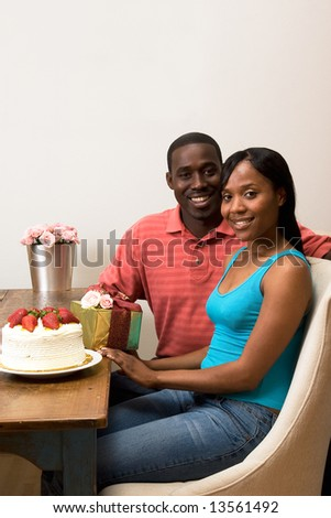 Attractive smiling couple celebrating a birthday sitting at a table.  On top of the table is a frosted cake with strawberries, a wrapped gift, and flowers.