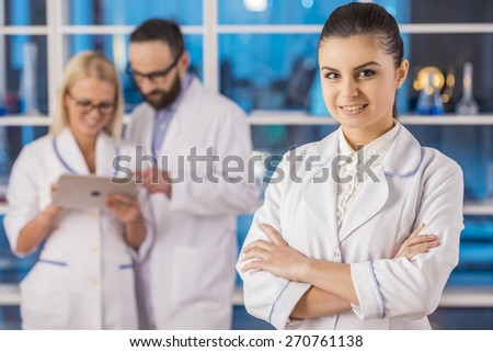 Attractive smiling fe male scientist looking at camera  on the background her colleague at the laboratory. - stock photo
