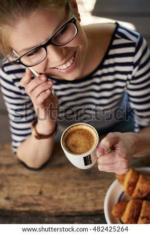 Attractive smiling female holding coffee mug and talking on mobile phone. Concept of business, lifestyle and mobility.