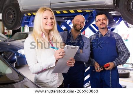 Attractive smiling female insurance agent discussing with auto mechanics renewal of car. Focus on girl