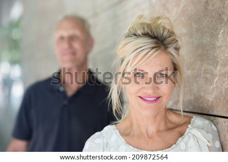 Attractive smiling friendly middle-aged woman with her long blond hair held up loosely around her face standing against a receding wall looking at the camera - stock photo
