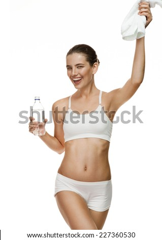 Attractive smiling girl holding water bottle and white towel / portrait of mixed race Latina Caucasian healthy sport brunette fitness girl - isolated on white background.  - stock photo